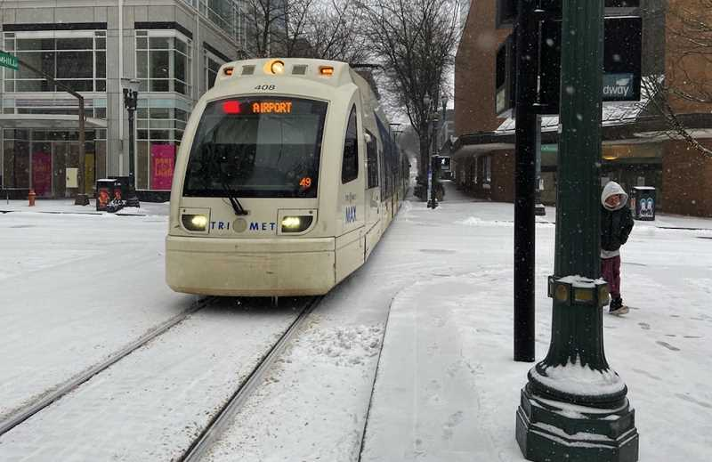 PMG PHOTO: DANA HAYNES - The MAX light rail train to Portland International Airport glides to a stop at Pioneer Courthouse Square, as a commuter hurries through the snow to reach the stop. , Portland Tribune - News The winter storm warning remain in effect as freezing rain is predicted to fall in much of the Portland region. Friday opens with blanket of snow