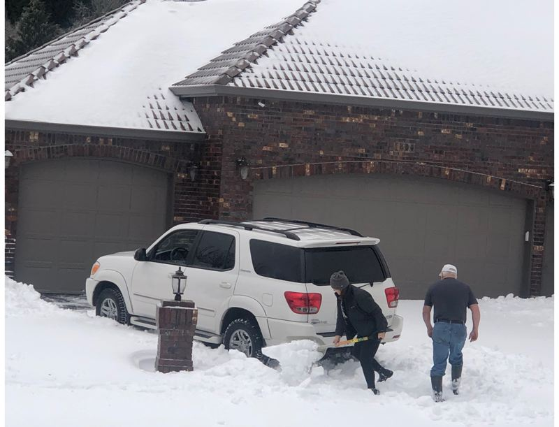 PMG PHOTO: MARK GARBER - Matt and C.J. Wetherbee dig their way out of their Gresham driveway, before a trek to Home Depot in order to fix a broken pipe.