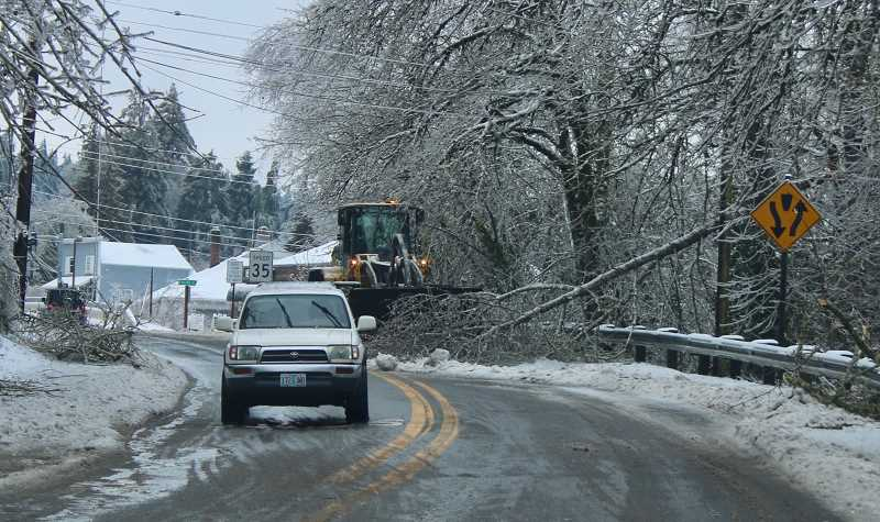 PMG PHOTO: J. BRIAN MONIHAN - Crews continued to work Saturday to clean up hazards and debris from the snow and ice storm.