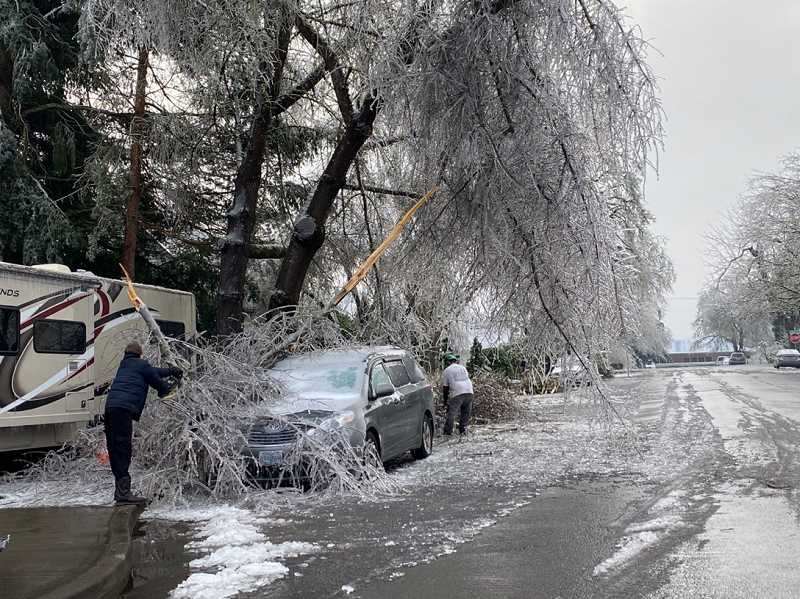 PMG PHOTO: KRISTEN WOHLERS - Canby residents remove debris from their homes, cars and roads on Sunday, Feb. 14.