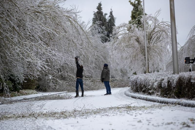 PMG PHOTO: JAIME VALDEZ - Two people clear branches that fell on the eastbound lane of SW Wilsonville Road.