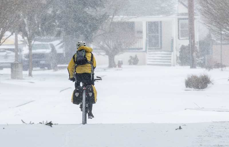 PMG PHOTO: JONATHAN HOUSE - A cyclist takes to the snowy streets in Southeast Portland. All transit services were heavily scaled back and Portland area schools canceled Tuesday, Feb. 15, as widespread power outages lingered after an ice and snow storm.
