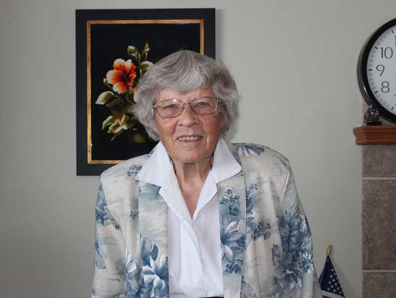 HOLLY SCHOLZ/MADRAS PIONEER    - Feturah Miller and her late husband, Jack, were missionaries in Vietnam, Thailand and the Philippines. She often admires the floral needlework wall hanging that she brought back from Vietnam, pictured behind her. She turns 100 on Sunday.
