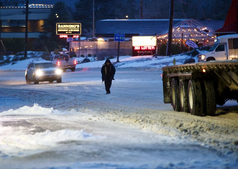 PMG PHOTO: JAIME VALDEZ - A man trudges through the snow along Highway 99W in Tigard as road conditions deteriorate late Friday, Feb. 12.