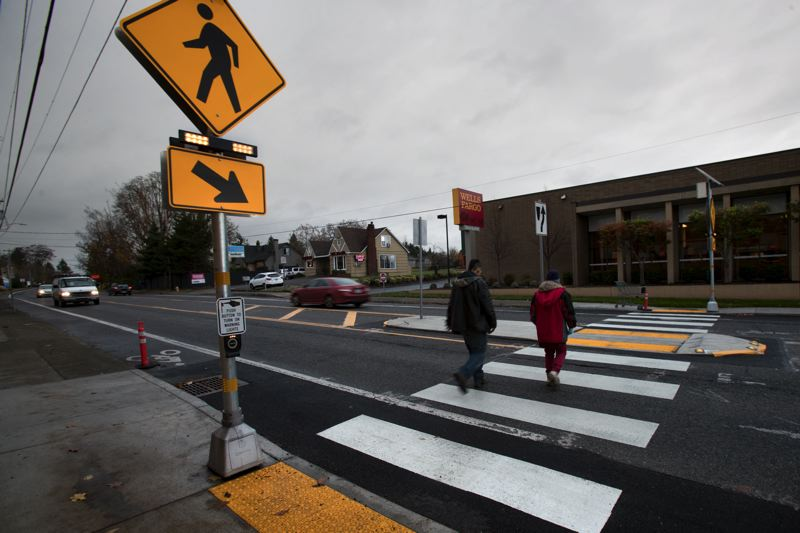 PMG PHOTO: JAIME VALDEZ - Pedestrians walk through the crosswalk at Southwest Hall Boulevard near Jo-Ann Fabrics after it was improved in 2017.