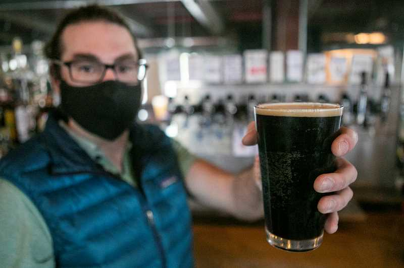 PMG PHOTO: JAIME VALDEZ - Holding a glass of Kates Nutty Shutdown Brown ale, Chris Sjolin said he doesnt side with groups like Open Oregon when it comes to rer
