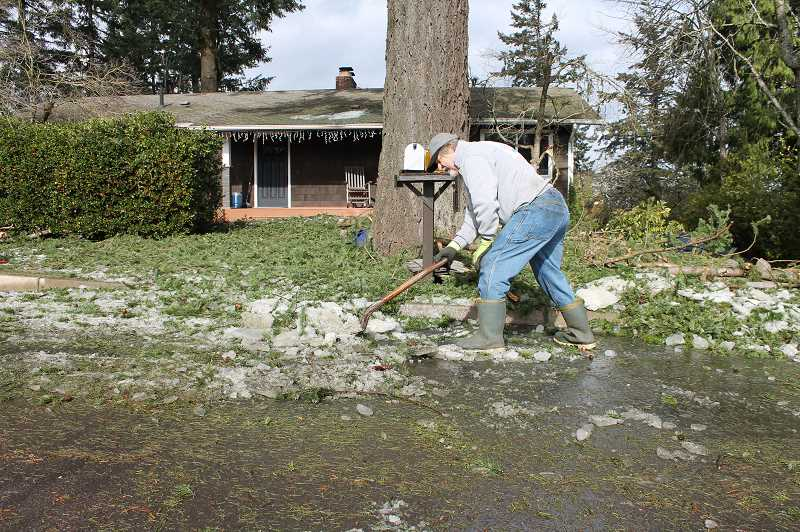 PMG PHOTO: HOLLY BARTHOLOMEW - Bernie Kuther clears away debris infront of his home on Valley View Drive.
