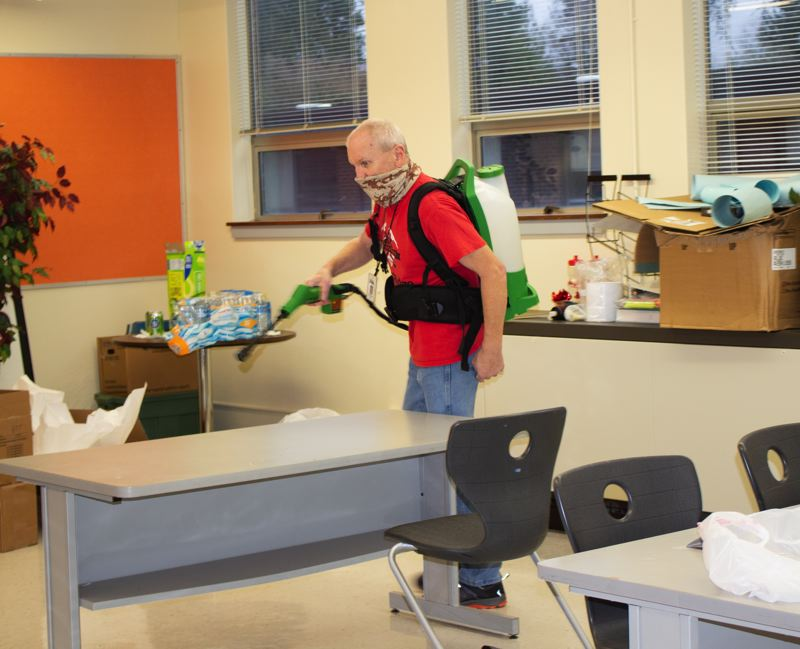COURTESY PHOTO: OREGON TRAIL SCHOOL DISTRICT/JULIA MONTEITH - Custodian Andy Jackson helps sanitize a classroom at Cedar Ridge Middle School where the district is now offering limited in-person instruction to select students.