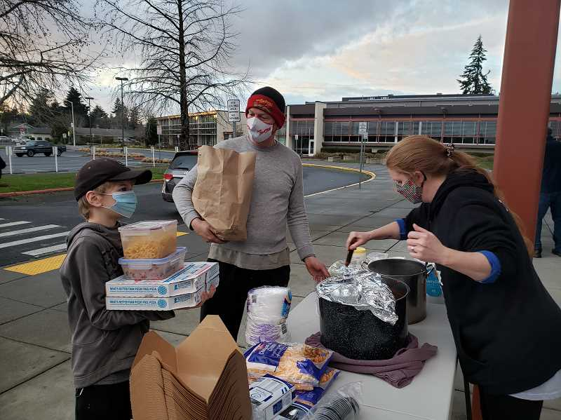 COURTESY PHOTO - Ginger Zimtbaum (right), one of the organizers of the community effort, serves hot meals on Feb. 17 to those without electricity at Gladstone High School.