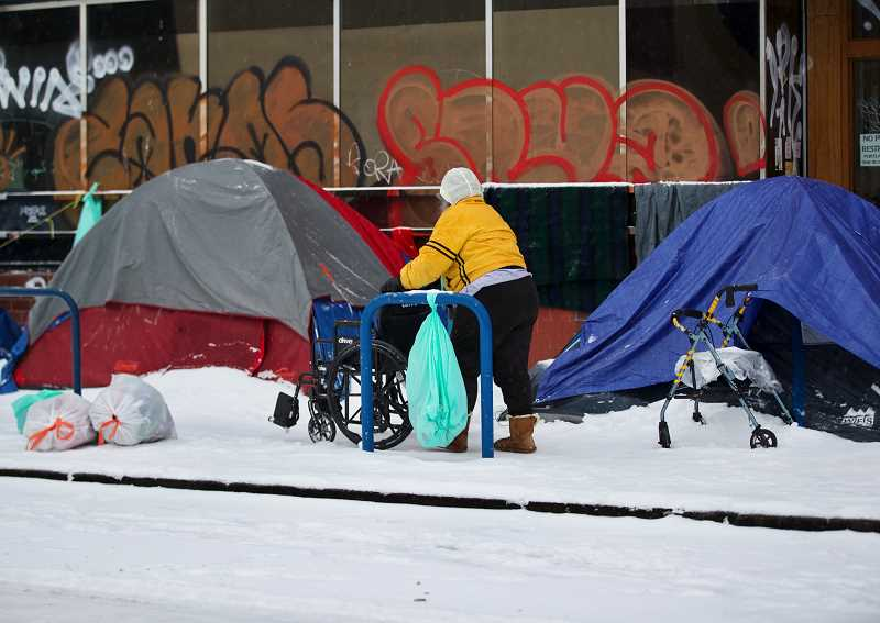 PMG PHOTO: JAIME VALDEZ - A homeless person walks gingerly along Southwest Broadway on Friday, Feb. 12, during a rare snow storm in  Portland. The city and county are seeking community proposals for alternative shelter options.
