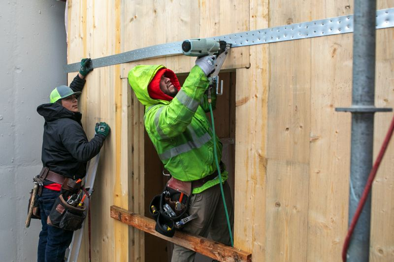 PAMPLIN MEDIA GROUP: JAIME VALDEZ - Workers continue in freezing temperatures of Waechter Architecture's three-story mixed-use office building on Mississippi Ave in North Portland.