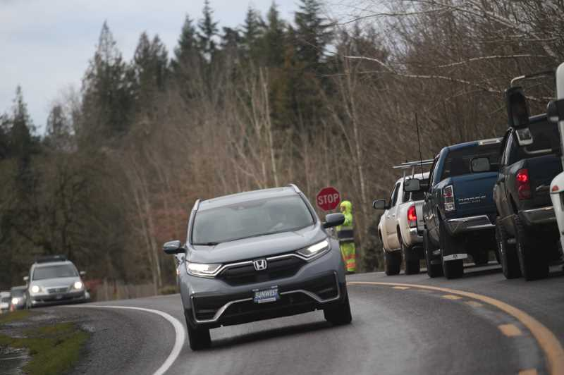 PMG PHOTO: PHIL HAWKINS - Flaggers control highway traffic as crews clear debris in the aftermath of a heavy ice storm that pelted much of the Willamette Valley Feb. 12-13.