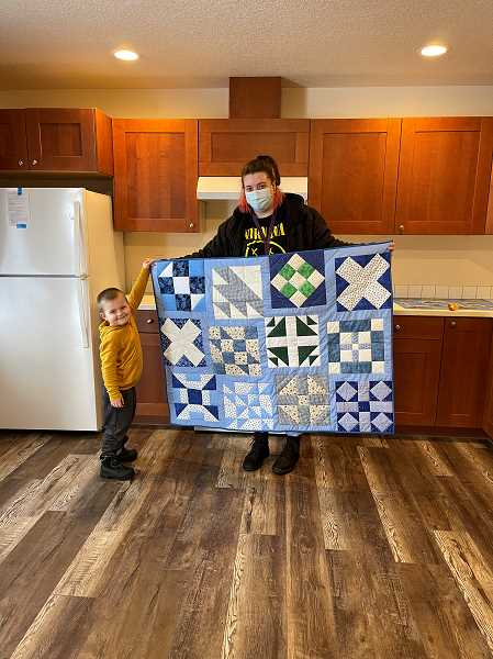COLUMBIA COUNTY HABITAT FOR HUMANITY - Gentry Harris and her son hold up a quilt donated by a local church group.