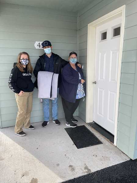 COLUMBIA COUNTY HABITAT FOR HUMANITY - Kaylee, Ben, and mom Ginny Carlson stand at the door to their new home.