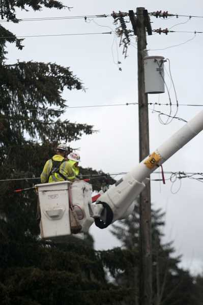 PMG PHOTO: PHIL HAWKINS - Work crews are lofted up to restore power along Highway 99E between Gervais and Brooks on Friday morning. Thousands of PGE customers remain without power a week after ice storms knocked out electricity to more than half a million people in the Willamette Valley.