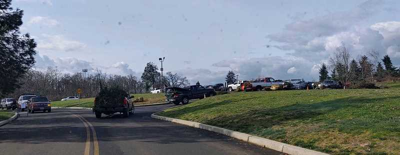 PMG PHOTO: RAYMOND RENDLEMAN - Cars loaded with tree debris line up to use the dumping site at Clackamas Community College in Oregon City. The site soon had to be closed due to overuse, and City Commissioner Rachel Lyles Smith shared the message of another site available at the Clackamette Cove.
