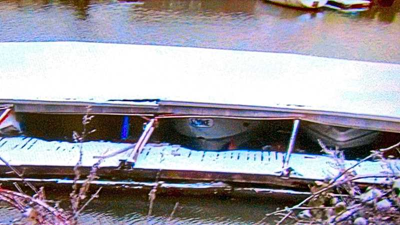 COURTESY KPTV FOX-12 NEWS - This close-up view from the shore shows the collapsed boat awning, and some of the 40 to 50 boats under it; many were sunk, and the rest were damaged.