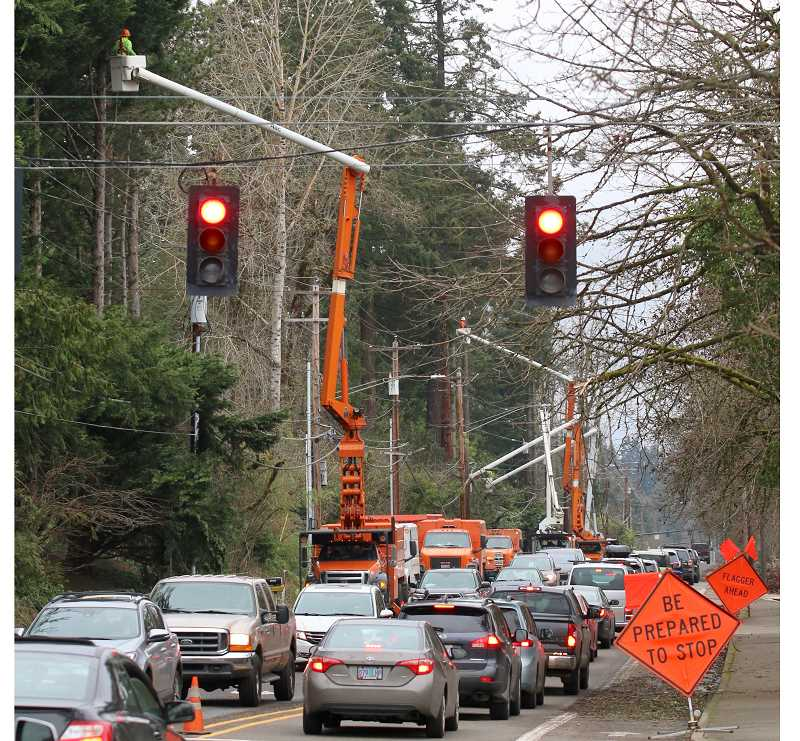 PMG PHOTO: BRIAN MONIHAN - Crews from Asplundh cut back branches from powerlines along Highway 43 in West Linn.