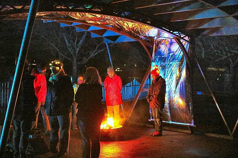 DAVID F. ASHTON - After a stroll along the Oaks Amusement Park Midway, guests spent a moment or two by a warming fire, burning near the Kaleidoscopic Canopy installation.