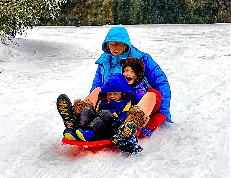 PAIGE WALLACE - Celeste Smith joined her children for a joyous sledding run down the driveway of their home, in the Creston-Kenilworth neighborhood.