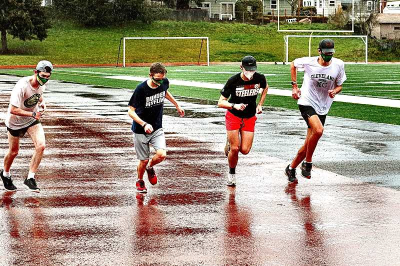 DAVID F. ASHTON - Even on their day off, and in the rain, CHS Track athletes - senior Nate Bone, junior Aidan Mackie, sophomore Tucker Swinth, and junior Toby Finn - headed out for a run at the Cleveland High Warriors Stadium.