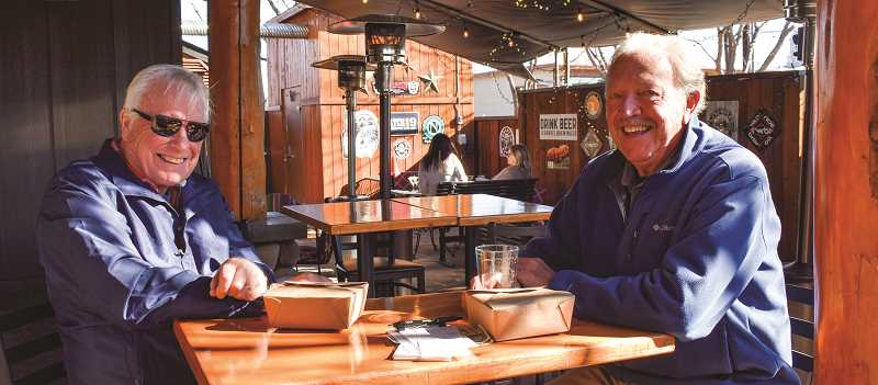 RAMONA MCCALLISTER - Forest Carbaugh, left, and Stanley Flynn enjoy an afternoon meal on the patio at Dillon's Grill the first week of reopening outside dining and takeout.