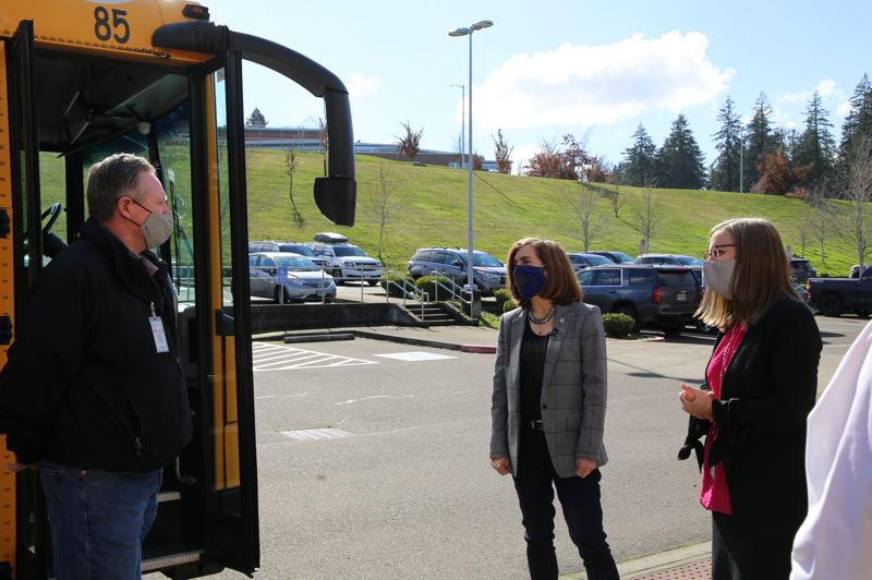 POOL PHOTO: STATESMAN JOURNAL - Oregon Gov. Kate Brown, center, talks with a bus driver during a Feb. 24 visit to a West Salem elementary school. Brown is reducing the risk levels for some counties beginning in late February.