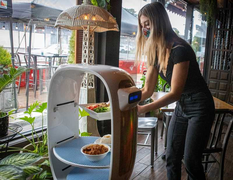 PMG PHOTO: JAIME VALDEZ - River, a server at Bistro Royale in Beaverton, demonstrates how a customer would receive their dish by the restaurants robot.