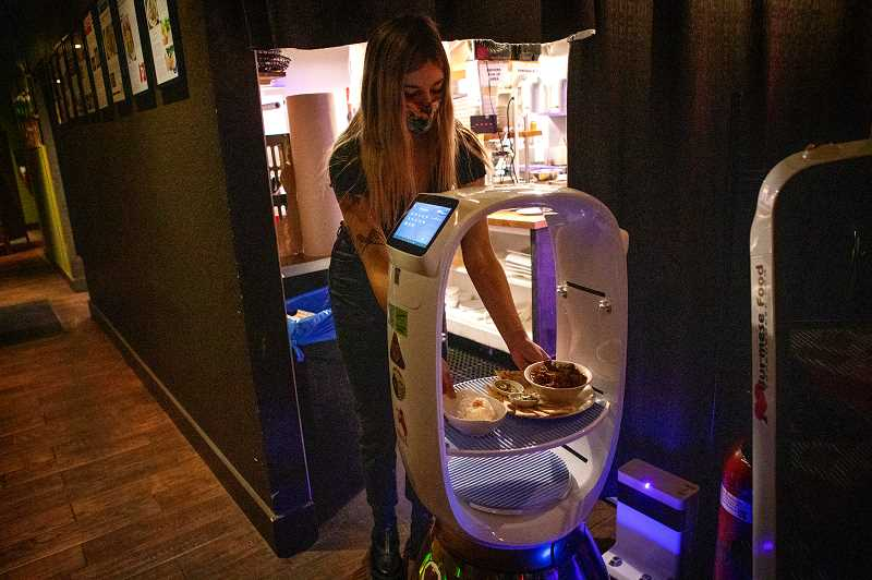 PMG PHOTO: JAIME VALDEZ - River, a server at Bistro Royale in Beaverton, places food on a tray of the restaurants robot that will deliver the food to customers table.
