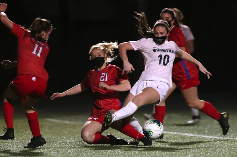 PMG PHOTO: JAIME VALDEZ - La Salle Prep's Gabby Warta (21) disrupts Wilsonville's Lindsey Antonson (10) from passing the ball in Thursday's soccer match. Wilsonville won, 4-0.
