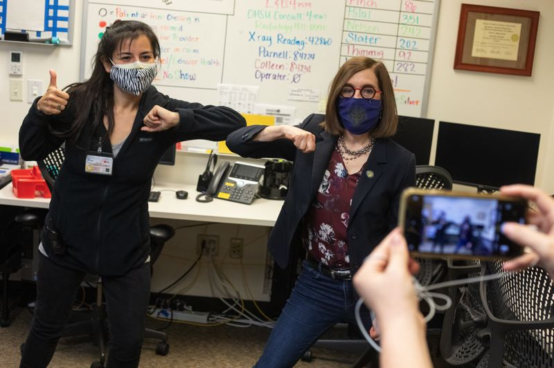 PMG PHOTO: JONATHAN HOUSE - Oregon Governor Kate Brown gives an elbow bump to medical assistant Blanca Vasquez after receiving the single-shot Johnson & Johnson Covid-19 vaccine at the OHSU Primary Care Clinic in Scappoose, Oregon.