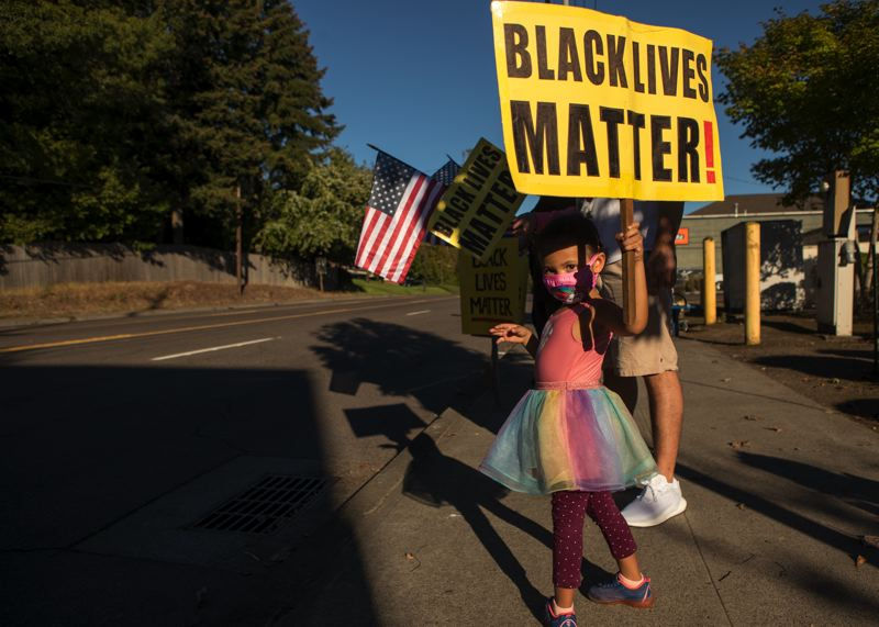 PMG PHOTO: JAIME VALDEZ - A child holds a Black Lives Matter sign during a vigil in Raleigh Hills following the death of George Floyd. State lawmakers are considering legislation on possible reparations for slavery.