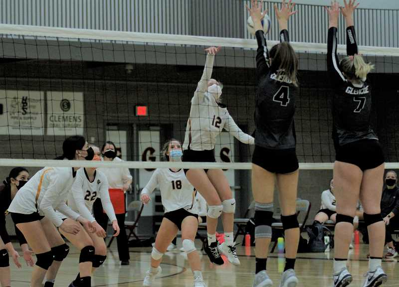 PMG PHOTO: WADE EVANSON - Sophomore outside hitter Chloe Hefner goes up for a kill while her teammates Jennifer Rodriguez (left), Abbigail Klaus (22), and Hannah Carlson (18) prepare for a return during the Vikings' game against Glencoe Tuesday night, March 9, at Forest Grove High School.