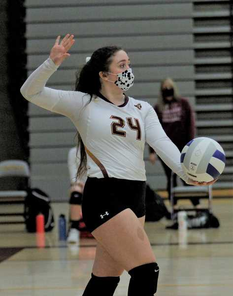 PMG PHOTO: WADE EVANSON - Forest Grove junior libero Faith Stavens serves during the Vikings' game against Glencoe Tuesday night, March 9, at Forest Grove High School.