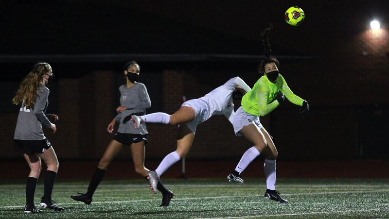 PMG PHOTO: MILES VANCE - Tualatin sophomore goalkeeper Olivia Poulivaati knocks the ball away following a header by Oregon City junior midfielder Jayne Rust at Tualatin High School on Wednesday, March 10.