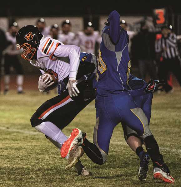 PMG PHOTO: LON AUSTIN - Molalla receiver Jacob Watson makes a move on two Crook County defenders after hauling in a pass from quarterback Isaac Thomas Klementis in Friday night's loss to Crook County.