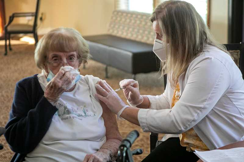 PMG PHOTOS: JAIME VALDEZ - Helen Buck receives her COVID-19 shot from a Safeway pharmacist Tuesday morning at Summerfield Estates Retirement Community.