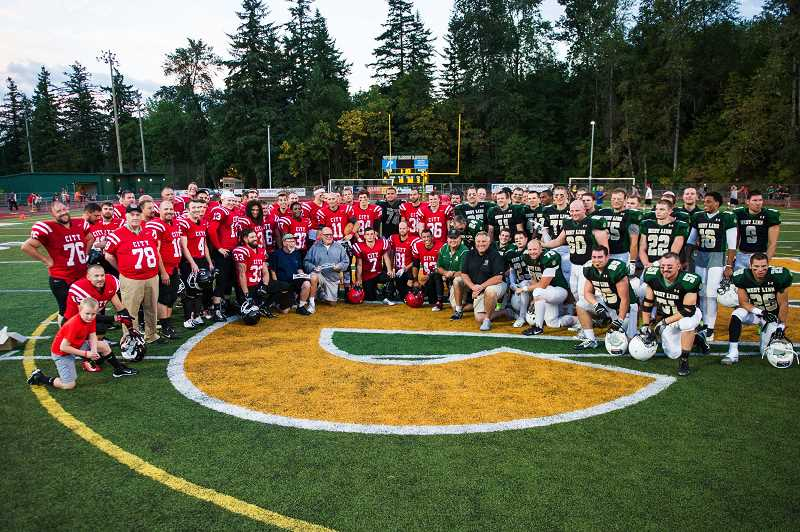 JOHN LARIVIERE - Oregon City and West Linn Battle for the Bridge alumni players join together to pose for a photo with Battle Hall of Fame inductees John Denny, Ed Burton, Joe Cerny and Ron Chappell during halftime ceremonies of the 2015 Battle for the Bridge Alumni Football Game. The alumni players are intense rivals during the game, but off the field they have become good friends as they come together in the battle to eradicate cystic fibrosis.