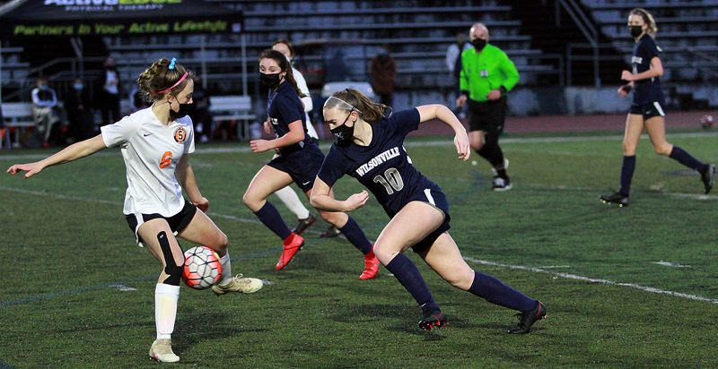 PMG PHOTO: MILES VANCE - Wilsonville's Lindsey Antonson (right) tries to work past Scappoose's Peyton Lennox during the Wildcats' 3-0 win at Wilsonville High School on Thursday, March 18.