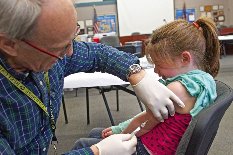 PMG FILE PHOTO: JAIME VALDEZ - James Mabry, a nurse with the Multnomah Education Service Department, gives a child her shot before the 2015 vaccination deadline.