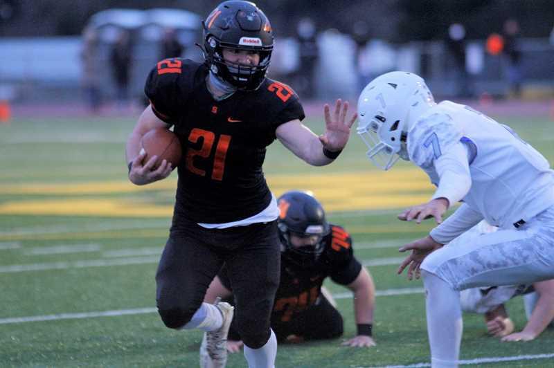 PMG PHOTO: WADE EVANSON - Scappoose running back DEACON SMITH fights-off Hillsboro defender Nahum Chavez during the Indians' game against the Spartans Friday, March 19 at St. Helens High School.