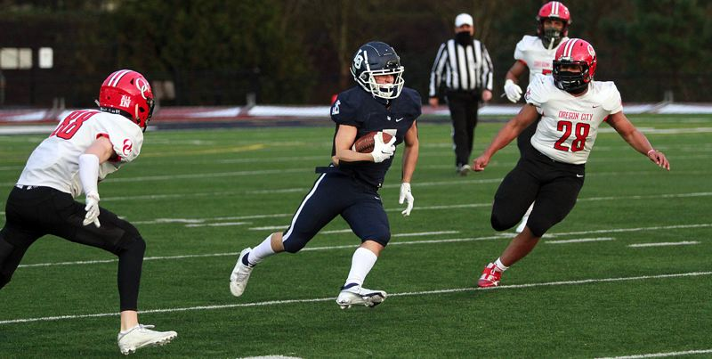 PMG PHOTO: MILES VANCE - Lake Oswego junior Gabe Olvera makes a cut during his team's 42-20 win over Oregon City on Friday, March 19, at Lake Oswego High School.