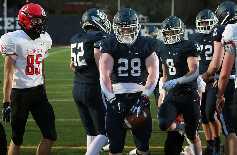 PMG PHOTO: MILES VANCE - Lake Oswego's Zach Mahan flexes after scoring one of his two touchdowns during the Lakers' 42-20 win over Oregon City at Lake Oswego High School on Friday, March 19.