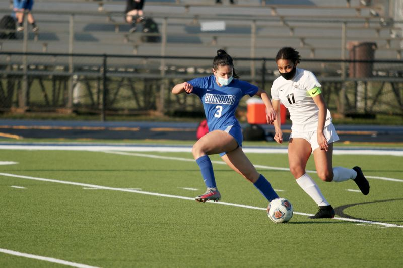 PMG PHOTO: PHIL HAWKINS - Woodburn senior forward Yahaira Rodriguez races upfield with Crescent Valleys Jada Foster for a potential scoring opportunity in the first half of the Bulldogs 2-1 loss to the Raiders.