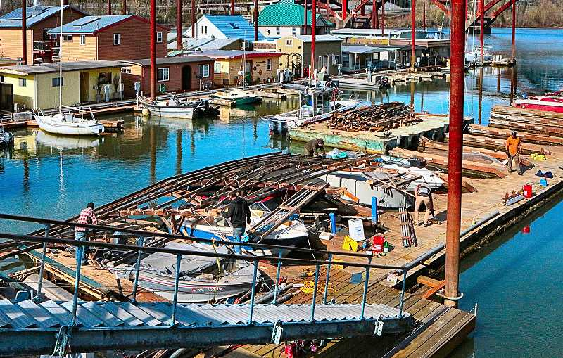 DAVID F. ASHTON - After a weekend of cleaning up debris around the dozens of sunken boats, workers still had quite a ways to go - to remove the collapsed steel roofing and supporting timbers from the docks at the Portland Rowing Club moorage, just south of the Sellwood Bridge.
