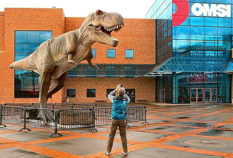 DAVID F. ASHTON - Outside the Oregon Museum of Science and Industry, a guest stops to photograph this giant beast, a full-sized Tyrannosaurus Rex, posted there as a signal that the new exhibition Dinosaurs Revealed is now on display inside.