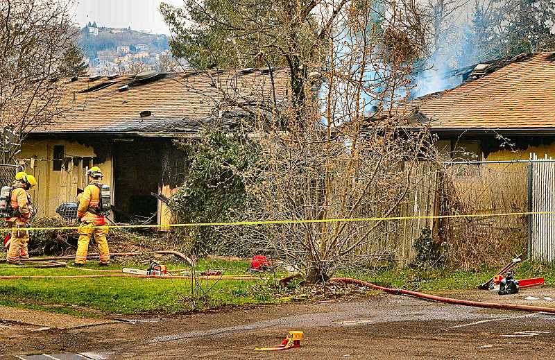 DAVID F. ASHTON - Standing by at the back of Brentwood-Darlington four-plex, firefighters kept watch for fire flare-ups - near where the deadly blaze killed one resident.