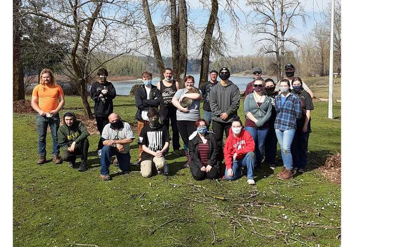 COURTESY PHOTO - Oregon City Rotary Club members and Oregon City High School students stabilize trees with native plantings during a March 13 work day at Oregon City's Clackamette Park.