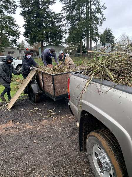 COURTESY PHOTO - On March 20, Oregon City Optimist Club and high school volunteers helped 50 households who lacked the equipment necessary to haul fallen trees and branches from their properties.