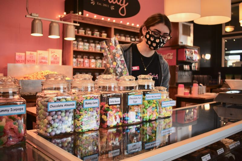 PMG PHOTO: TERESA CARSON - Tricia Hooley, gets ready to bag up some Easter treats at iCandy in downtown Gresham. She said customers seem more optimistic recently.